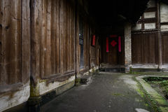Shady path before ancient wood structural dwelling building Royalty Free Stock Photo