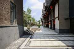 Shady pavement before archaised Chinese buildings with lanterns Royalty Free Stock Photos