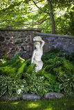 Shady perennial garden. Lush green summer garden with perennial plants and statue near stone wall Royalty Free Stock Photo