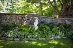 Shady perennial garden. Lush green summer garden with perennial plants and statue near stone wall Royalty Free Stock Photography