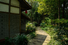 Shady planked path outside Chinese traditional houses in sunny a Stock Photography