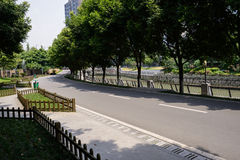 Shady riverside asphalt road in city on sunny summer day Stock Images