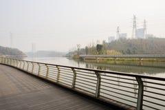 Shady riverside footbridge near city in sunny winter afternoon. Shady riverside footbridge near modern city in sunny winter afternoon,Chengdu,China stock image