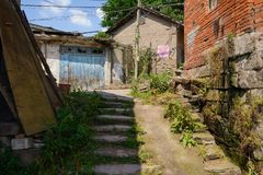 Shady stone steps to street in aged houses on sunny summer day Stock Photo