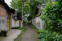Shady unpaved alley between Chinese ancient houses in summer gre Royalty Free Stock Image