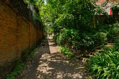 Shady unpaved alley between red-brick wall and farmhouses in sun Stock Photo