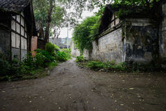 Shady unpaved path between ancient Chinese buildings in verdant Royalty Free Stock Photo