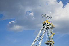 Shaft mine. Shaft tower of a coal mine with dark clouds and blue sky Royalty Free Stock Photo
