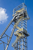 Shaft mine. Shaft tower of a coal mine with white cloud and blue sky Royalty Free Stock Image