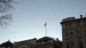 The shaft with the Russian state flag on the peak of gray justice building.  stock video footage