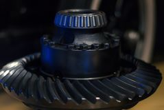 Shaft with tapered roller bearing and spiral bevel gear wheel. Massive metal detail - shaft with tapered roller bearing and spiral bevel gear wheel - on a dark royalty free stock photos