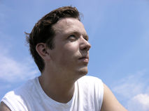 Shaggy. Young man looking at the Sun, sky background. Slightly desaturated Royalty Free Stock Image