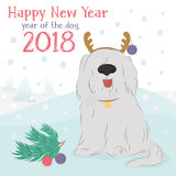 Shaggy dog with a decorative reindeer and Christmas balls. Christmas card with large, shaggy dog breed Bobtail with decorative reindeer and Christmas balls on a Royalty Free Stock Photography