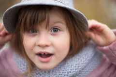 Shaggy girl in jacket, gray scarf and fedora hat Royalty Free Stock Images