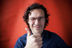 Shaggy man with glasses. Winking his right eye Stock Images