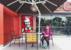 SHAH ALAM, МАЛАЙЗИЯ - 13-ОЕ АВГУСТА 2017: Женщины сидят на стуле вне известной жареной курицы Кентукки ресторана фаст-фуда Стоковое Изображение RF
