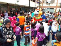 SHAH ALAM, MALAYSIA - AUGUST 12, 2017: Crowds of peoples with a mascot and an artist during BREAK THE COIN BOX PROGRAM. Parents, pupils, teachers in crowds with Royalty Free Stock Photo