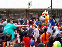 SHAH ALAM, MALAYSIA - AUGUST 12, 2017: Crowds of peoples with a mascot and an artist during BREAK THE COIN BOX PROGRAM. Parents, pupils, teachers in crowds with Stock Images