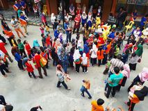 SHAH ALAM, MALAYSIA - AUGUST 12, 2017: Crowds of peoples with a mascot and an artist during BREAK THE COIN BOX PROGRAM. Parents, pupils, teachers in crowds with Stock Image