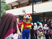 SHAH ALAM, MALAYSIA - AUGUST 12, 2017: Crowds of peoples with a mascot and an artist during BREAK THE COIN BOX PROGRAM. Parents, pupils, teachers in crowds with Royalty Free Stock Photography