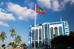Shaheedh Hussain Adam Building och flagga av Maldiverna i mitt av stadsmannen, huvudstad av Maldiverna Arkivbilder