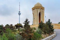 Shahidlar纪念碑或永恒火焰纪念碑在受难者`车道 并且电视塔在晚上 秃头 阿塞拜疆 库存照片