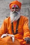 Shaiva sadhu (holy man). VARANASI - JANUARY 13: Shaiva sadhu (holy man) seeks alms in front of a temple on January 13, 2010 in Varanasi, State of Uttar Pradesh Stock Photography