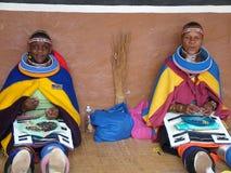 SHAKALAND,南非-大约2011年11月:未认出的祖鲁族人妇女做传统祖鲁族人成串珠状首饰 图库摄影