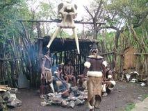 Shakaland Zulu Cultural Village, SUDAFRICA - CIRCA novembre 2011: Ballerini zulù non identificati del guerriero intorno ad un fuo fotografie stock libere da diritti
