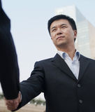 Shake hands. A businessman shake hands with a businesswoman Royalty Free Stock Photography
