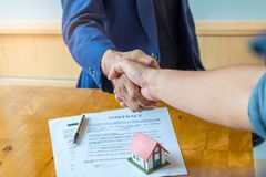 Shake hands for home trading. Between brokers and clients. Shake hands for home trading. Between brokers and clients,Model house and contract put on the table Stock Photography