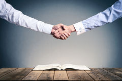 Shake hands on open books.  Royalty Free Stock Images