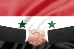 Shakehand d'homme d'affaires au-dessus de drapeau de la Syrie Photographie stock libre de droits