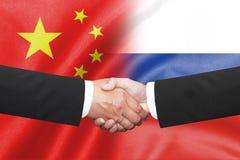 Shakehand d'homme des affaires deux sur la porcelaine et le drapeau russe Photos stock
