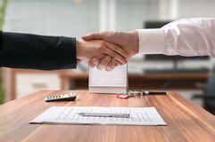 Shakehand of lawyer and business woman sitting behind desk with agreement Royalty Free Stock Image