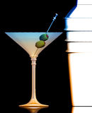 Shaken Not Stirred. The drink made famous in the James Bond movies. Double olive martini  and chrome shaker on black background Royalty Free Stock Image