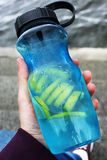 Shaker in hand. Lemon with water. stock image