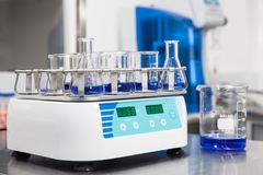Shaker loaded with erlenmeyers and beakers. Laboratory shaker loaded with erlenmeyers and beakers Royalty Free Stock Photo