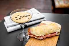 Shakerato drink with panini and newspaper. Royalty Free Stock Photos