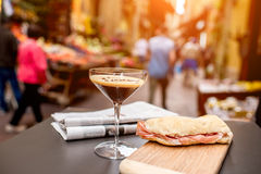 Shakerato drink with panini and newspaper. Royalty Free Stock Image