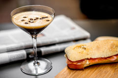 Shakerato drink with panini and newspaper. Royalty Free Stock Images