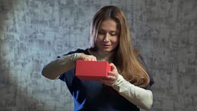 Beautiful girl opens a gift. She shakes the red gift box and opens it and pulls out a jewel case stock footage