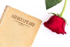Shakespeare book and red rose. An old book by Shakespeare and a red rose sit on a white background; symbol of love and passion Stock Photos