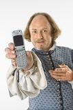 Shakespeare with cell phone. William Shakespeare in period clothing holding cell phone towards viewer Royalty Free Stock Photos