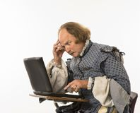 Shakespeare che per mezzo del computer portatile. Fotografia Stock