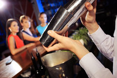 Shaking a cocktail. Waiter shaking a cocktail, young women on the background Stock Images