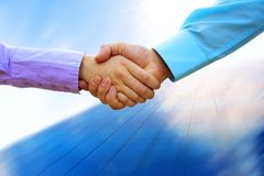 Shaking hands. Of two business people on blur business background