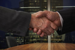 Shaking hands. Over boardroom table with city lights in background Royalty Free Stock Image