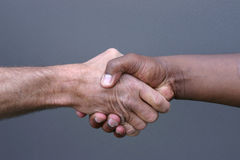 Shaking hands. A black man and white man shaking hands Royalty Free Stock Photography
