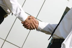 Shaking hands. Two young businessmen shaking hands in front of a building Royalty Free Stock Photography